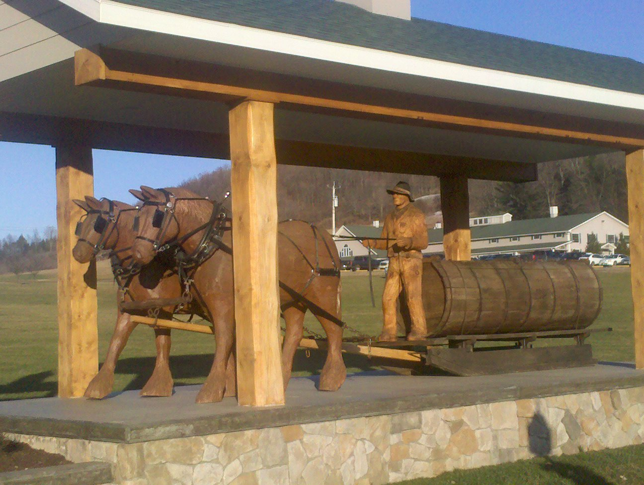 Wooden Sculptures of work horses pulling sap sled and farmer