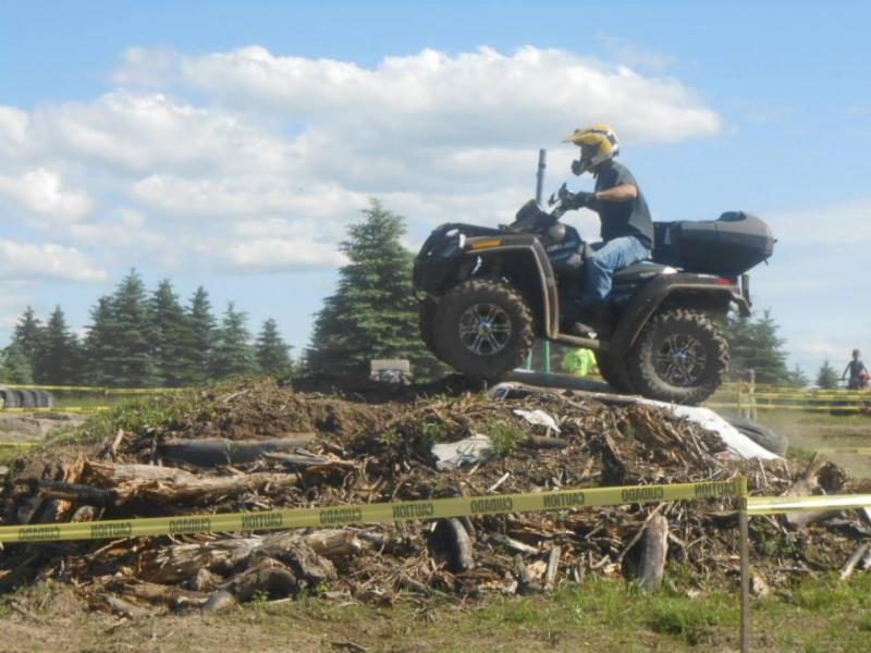 Rider on quad ATV going over a mound of debris at Tall Pines ATV Park